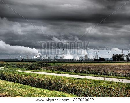 Industry, Smoke Stacks And Wind Turbines Behind A Green Field Under Dark Clouds Near Antwerp, Belgiu