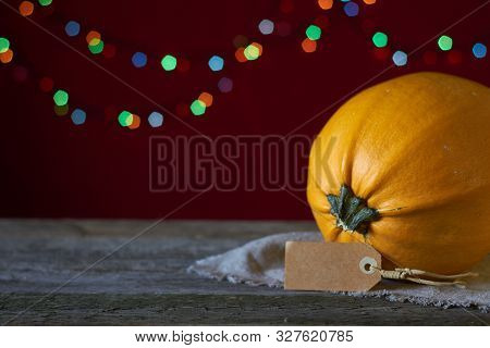 Autumn Background On A Dark Wooden Surface, Yellow Pumpkin On A Background Of Blurry Lights, Selecti