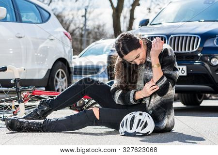 Full length of a young injured woman, sitting on the ground with severe pain at her elbow after bicycle accident next to parked cars on a busy street