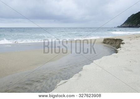 Beachscape, a cloudy afternoon a small stream of water flowing into the sea of a Caribbean beach, in Tayrona National Park, Colombia