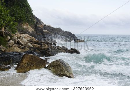 Beach landscape, waves coming against the rocks in the Colombian Tayrona National Park