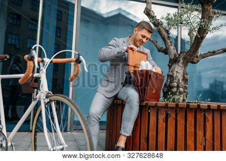 Businessman bicyclist puts document into briefcase poster