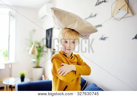 Pillow fight. Childs play. Mischievous preschooler child jumping on a sofa and hitting with pillows. Active games for kids at home. poster
