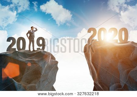 Businessman looking into future 2020 from 2019