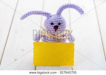 Lilac Knitted Bunny Holding A Yellow Card On The Light Wooden Background, Close-up. Place To Insert