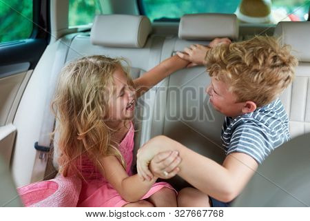 Two siblings argue and fight in the car in the backseat