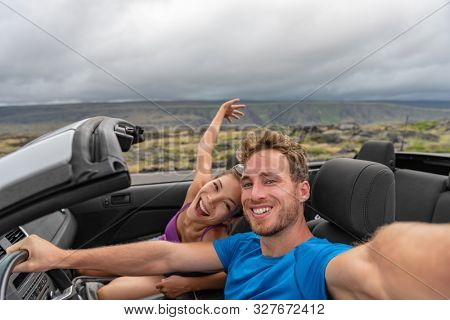 Car couple taking selfie photo with phone on road trip driving cabriolet sports car on summer vacation with arms up in fun. Asian girl, Caucasian man dancing in open roof car.