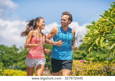 Active healthy runners couple running laughing talking together happy training buddy outside workout outdoors in summer park. Woman and man jogging.