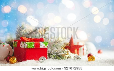 Christmas winter background with gift box, Christmas baubles and fir tree branches on snow.