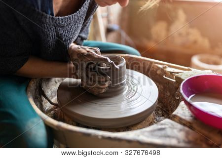 Hand made ceramics are formed by a young woman on a potters wheel