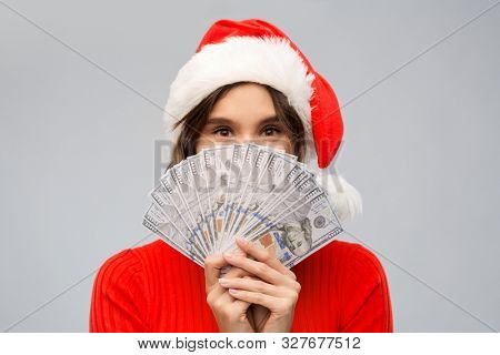 christmas, holidays and finance concept - happy young woman in santa helper hat hiding behind dollar money banknotes over grey background