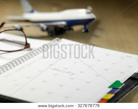 monthly planner woth airplane and glasses on the wooden table