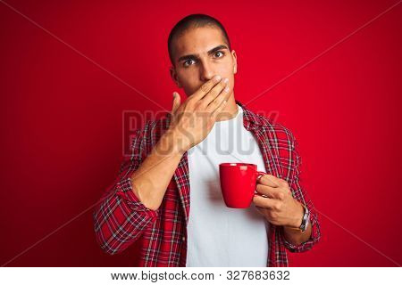 Young handsome man wearing shirt drinking a cup of coffee over red isolated background cover mouth with hand shocked with shame for mistake, expression of fear, scared in silence, secret concept