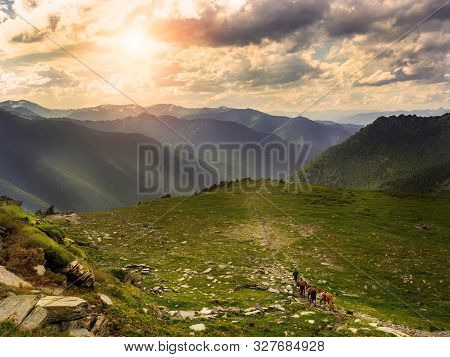 Beautiful Mountain Scenery Of The Sunset, Tourism On Horses, Bags With Provisions.