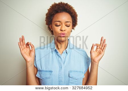 Young beautiful african american woman with afro hair over isolated background relax and smiling with eyes closed doing meditation gesture with fingers. Yoga concept.