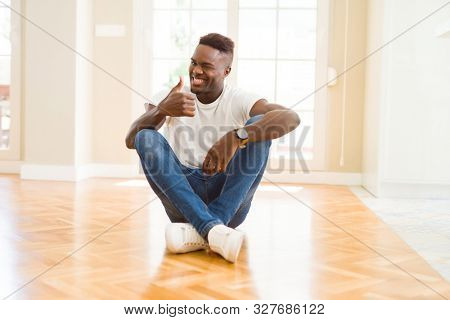 Handsome african american man sitting on the floor at home doing happy thumbs up gesture with hand. Approving expression looking at the camera with showing success.