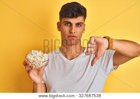 Young indian man holding pack of popcorn standing over isolated yellow background with angry face, negative sign showing dislike with thumbs down, rejection concept