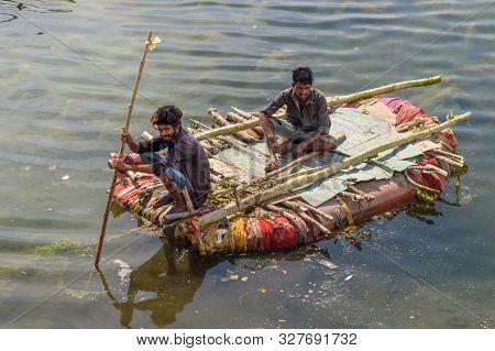 Udaipur, India - February 17, 2019: Indian Men Fishing On Raft On Swaroop Sagar Lake In Udaipur. Raj