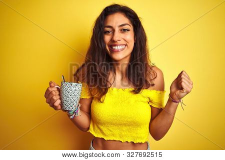 Young beautiful woman drinking cup of coffee standing over isolated yellow background screaming proud and celebrating victory and success very excited, cheering emotion