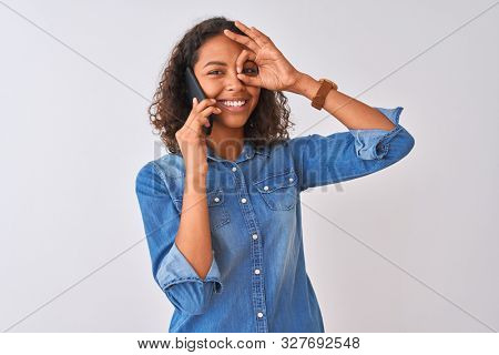 Young brazilian woman talking on the smartphone standing over isolated white background with happy face smiling doing ok sign with hand on eye looking through fingers