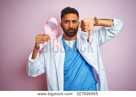 Young indian doctor man holding cancer ribbon standing over isolated pink background with angry face, negative sign showing dislike with thumbs down, rejection concept