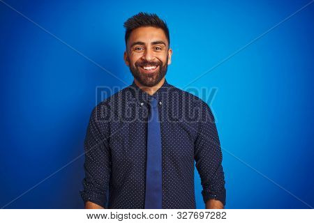 Young indian businessman wearing elegant shirt and tie standing over isolated blue background with a happy and cool smile on face. Lucky person.