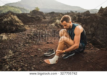 Male Runner Bandaging Injured Ankle. Injury Leg While Running Outdoors. First Aid For Sprained Ligam