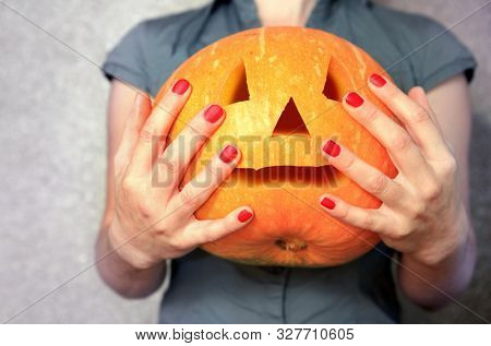 ripe pumpkin in hands of woman, useful vegetable for Halloween
