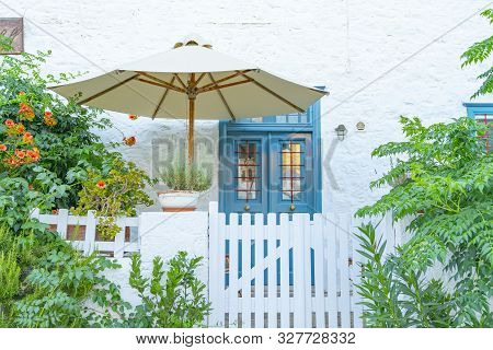Blue Front Door Under Shade Umbrella With Quaint White Fence, Gate And Garden Photographed From Stre