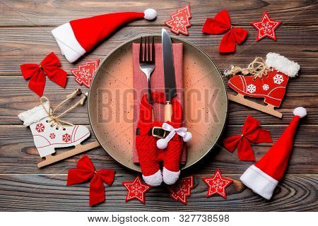 Holiday Composition Of Plate And Flatware Decorated With Santa Hat And Clothes On Wooden Background.