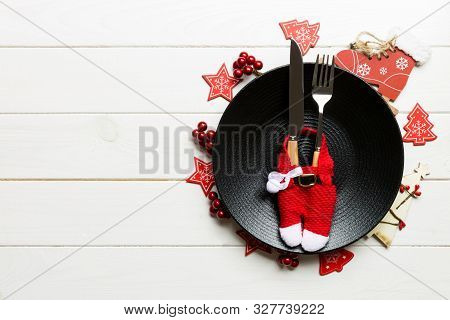 Holiday Composition Of Plate And Flatware Decorated With Santa Clothes On Wooden Background. Top Vie
