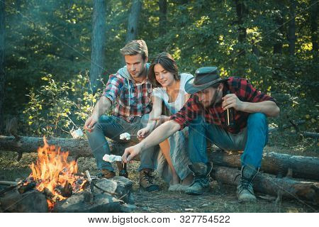 Group Of Backpackers Relaxing Near Campfire. Pleasant Weekend Near Campfire. They Are Sitting Around