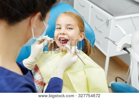 Female Dentist Examines Of Smiling Child At The Pediatric Dentistry Clinic.