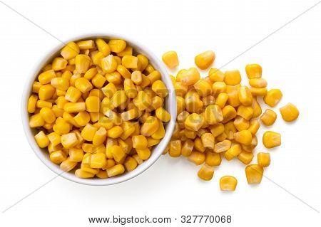 Canned Sweet Corn In A White Ceramic Bowl Next To Spilled Sweet Corn Isolated On White. Top View.