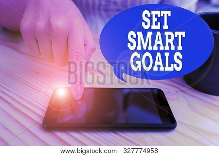 Text sign showing Set Smart Goals. Conceptual photo giving criteria to guide in the setting of objectives woman using smartphone office supplies technological devices inside home. poster