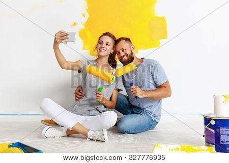 Young Happy Couple Is Repairing And Painting The Wall At Home