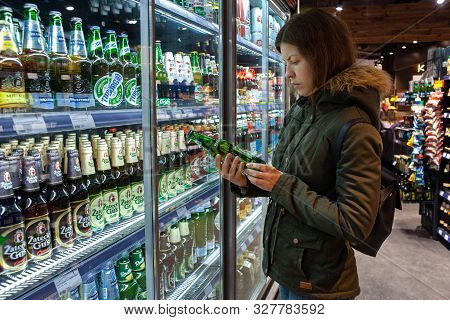 Minsk, Belarus - October 4, 2019: Woman Buys Alcohol In Grocery Store. Young Woman Reading Ingredien