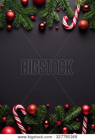 Black Christmas and New Year background. Decorative border of fir branches, Christmas balls and Candy canes
