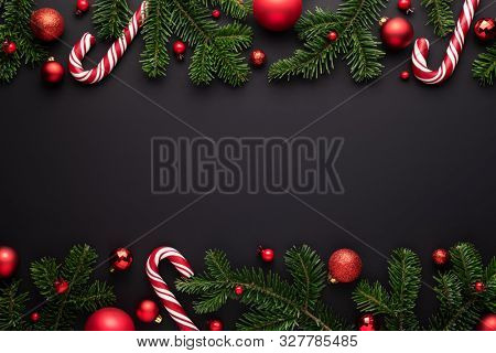 Black Christmas background. Decorative border frame of fir branches, red Christmas balls and Candy canes