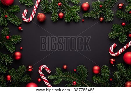 Black Christmas background. Decorative frame of fir branches, Christmas balls and Candy canes