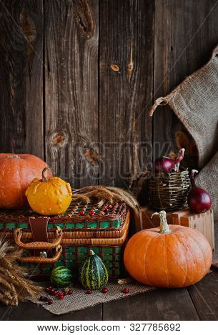 Happy Thanksgiving Background, Pumpkins And Wicker Basket On Old Wooden Table. Halloween. The Autumn