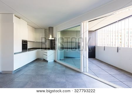 Modern white kitchen in empty apartment with white walls. Dark tiles. Nobody inside
