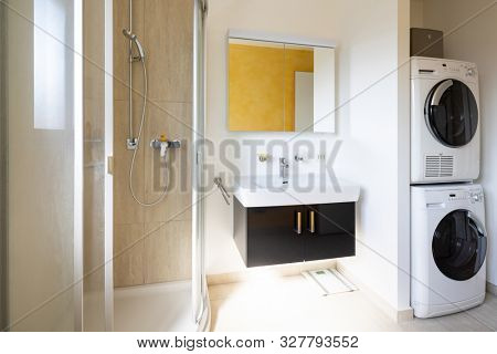 Modern bathroom with shower, black sink, washer and dryer. Nobody inside