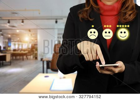 Businesswoman In Black Suit Pressing Smiling Face And Five Stars Emoticon On Mobile Phone For Evalua
