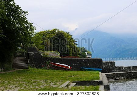 Southern Resort With Boats, Lake Como And Alps Mountains In Background.