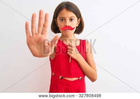 Beautiful child girl holding fanny party mustache standing over isolated white background with open hand doing stop sign with serious and confident expression, defense gesture