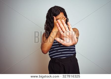 Transsexual transgender woman wearing striped t-shirt over isolated white background covering eyes with hands and doing stop gesture with sad and fear expression. Embarrassed and negative concept.