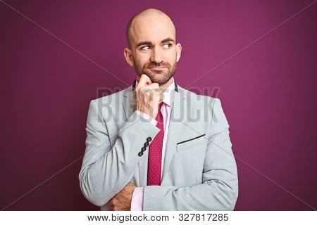 Young business man wearing suit and tie over purple isolated background with hand on chin thinking about question, pensive expression. Smiling with thoughtful face. Doubt concept.