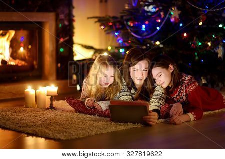 Mother And Her Two Cute Young Daughters Using A Tablet Pc At Home By A Fireplace In Warm And Cozy Li