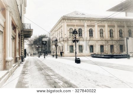 Winter ambient of snowy day in European city of Belgrade with passing passerby in the background and street lamps and European architecture building. poster